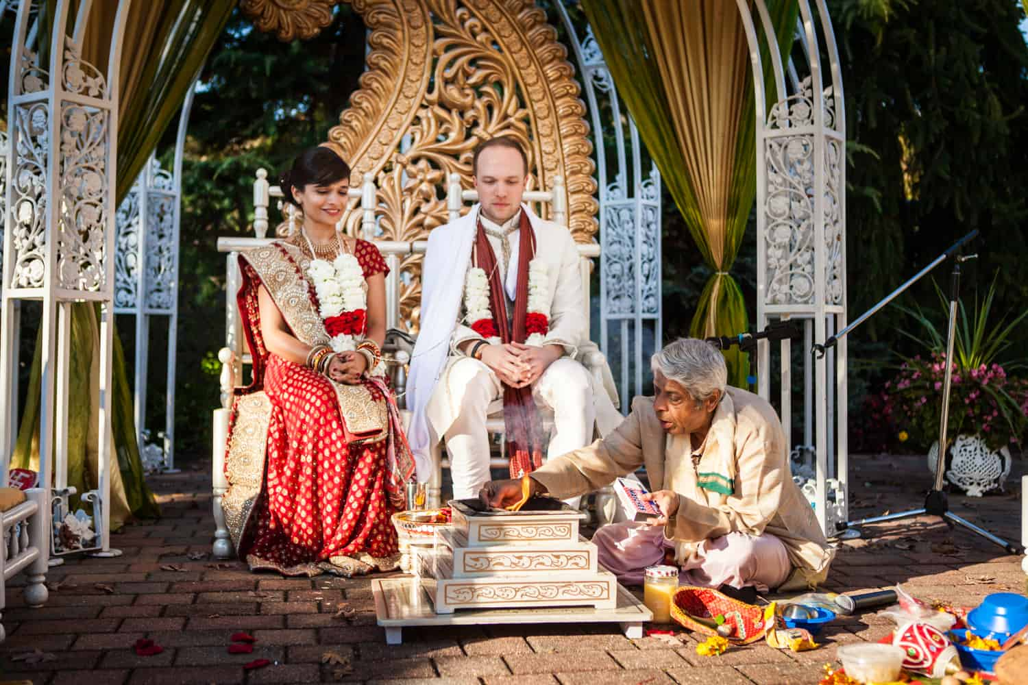 Bride and groom with priest during traditional Hindu wedding ceremony
