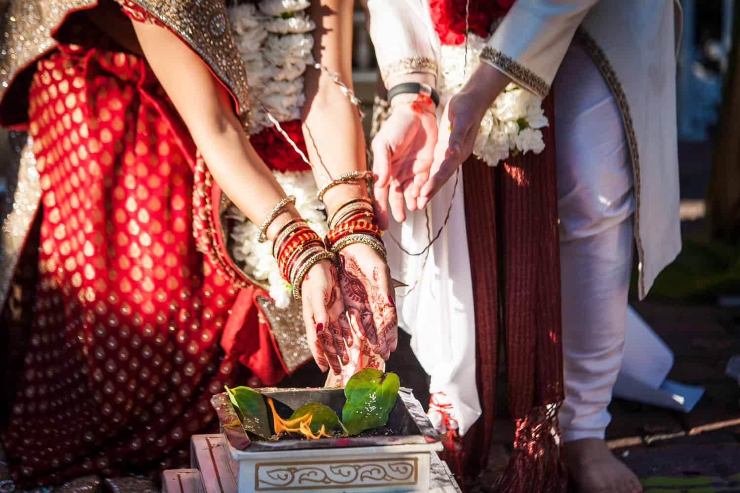 Close up on bride and groom's hands during traditional Hindu wedding ceremony