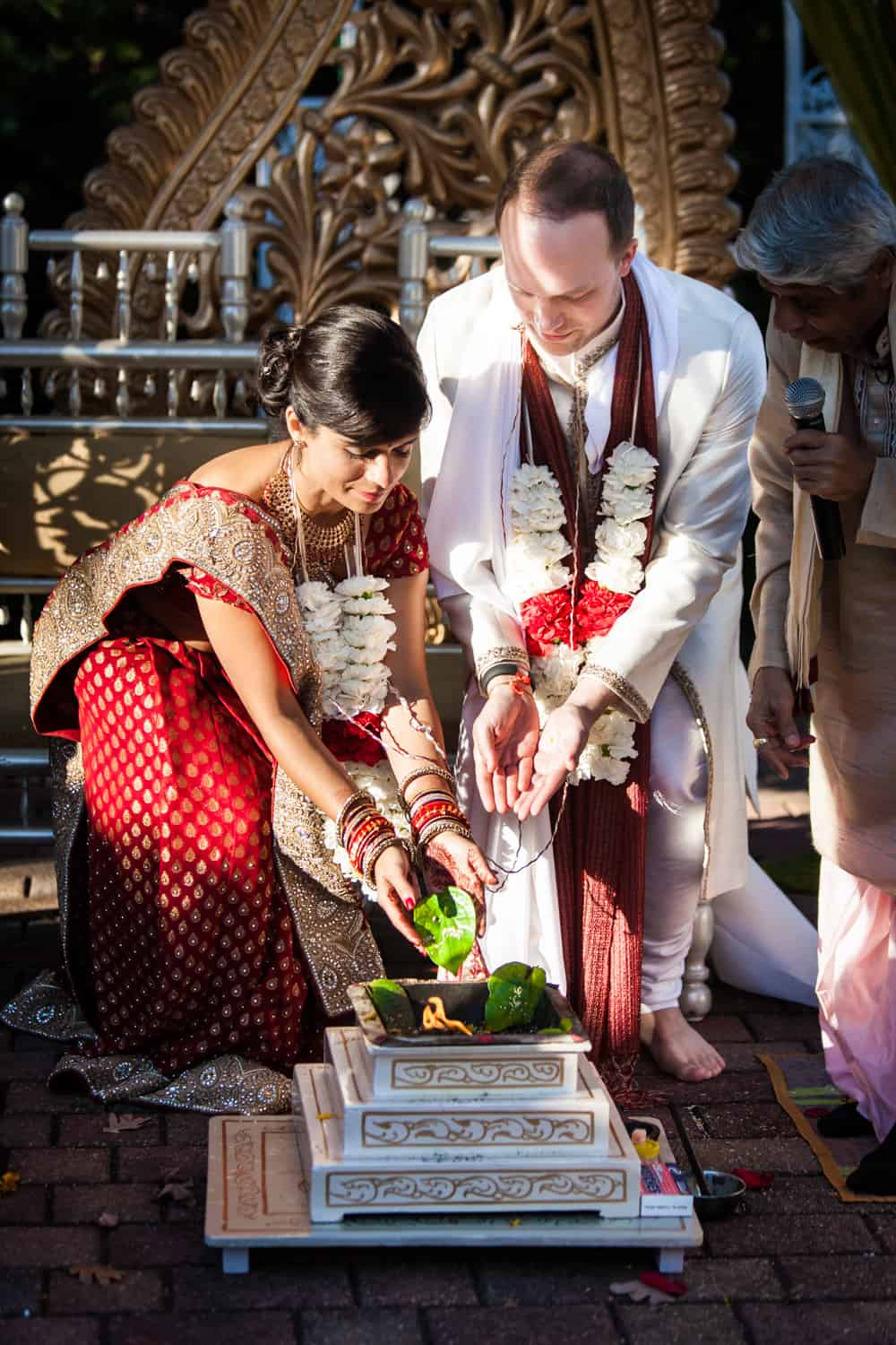 Bride and groom putting leaves in fire during traditional Hindu wedding ceremony