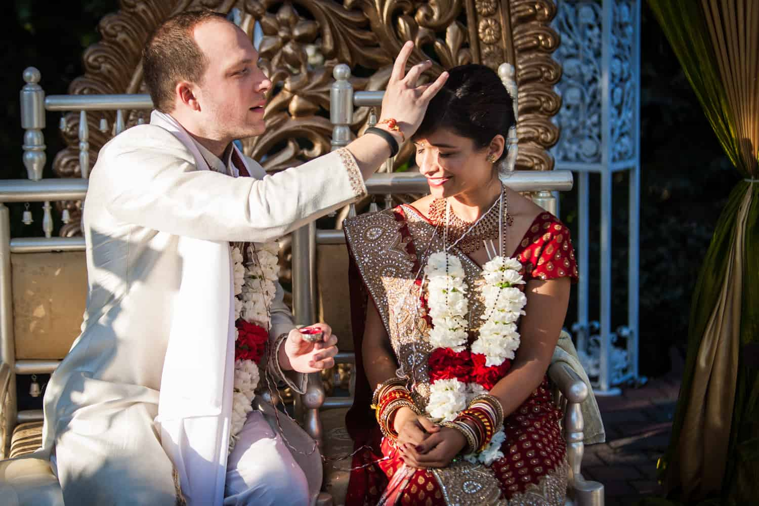 Groom putting bindhi on bride during traditional Hindu wedding ceremony
