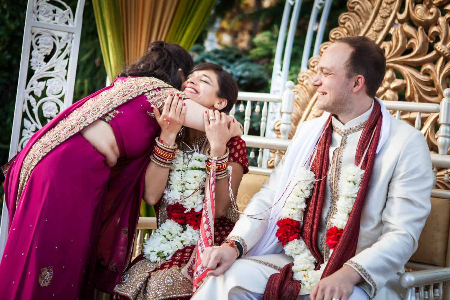 Mother hugging bride in front of groom during traditional Hindu wedding ceremony