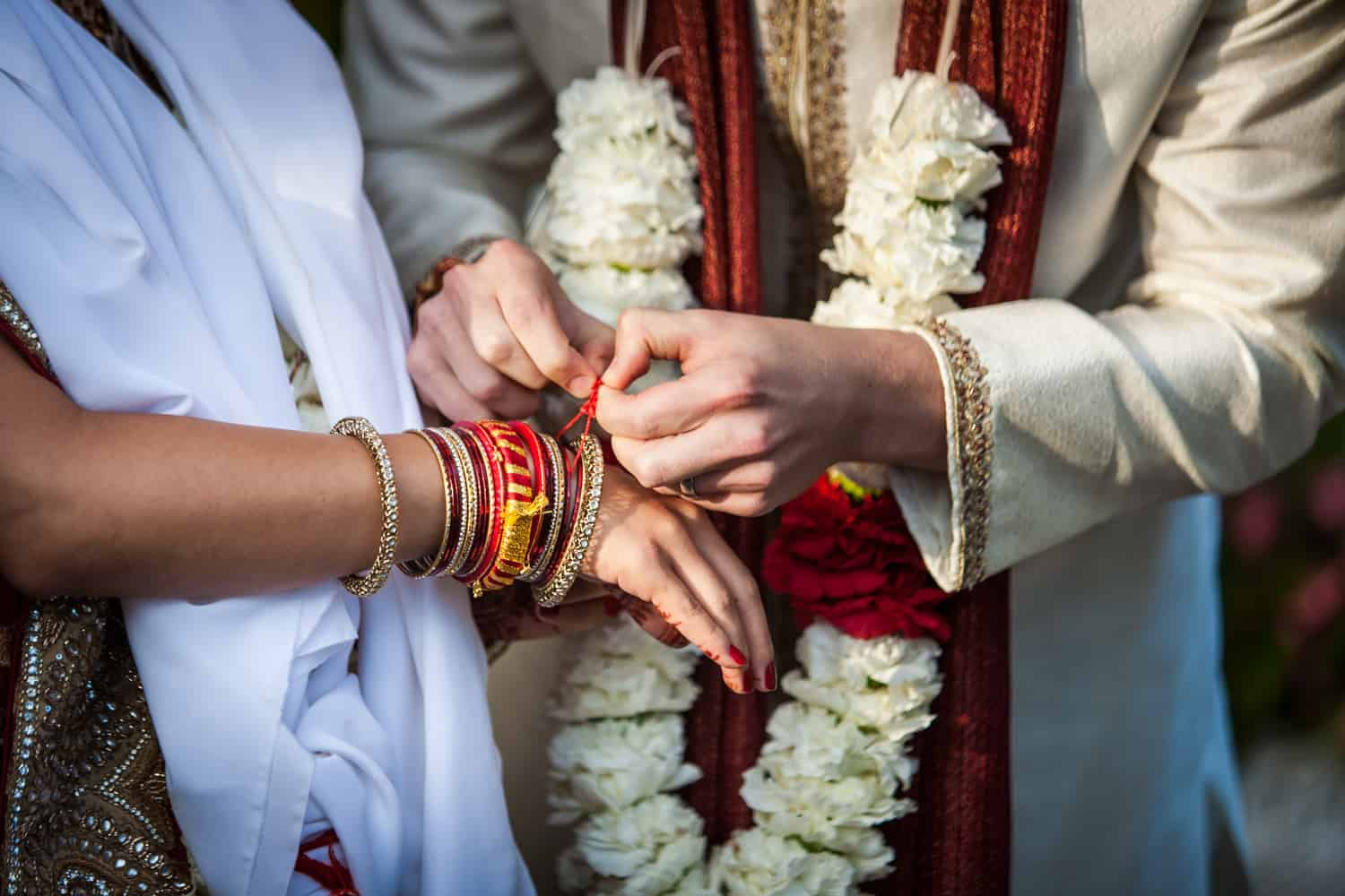 Close up of groom tying bracelet on bride during traditional Hindu wedding ceremony
