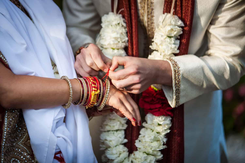 Close up of groom tying bracelet on bride during traditional Hindu wedding ceremony
