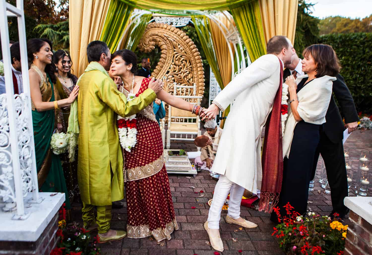 Bride and groom holding hands while kissing family members