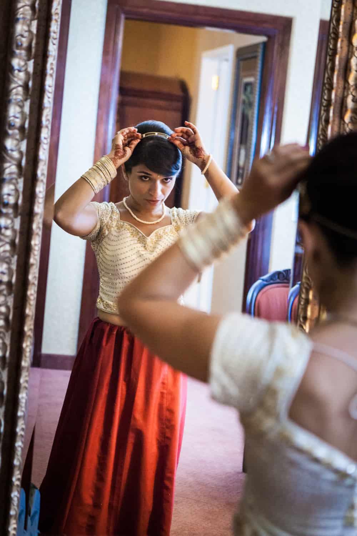 Bride adjusting hair accessory in mirror