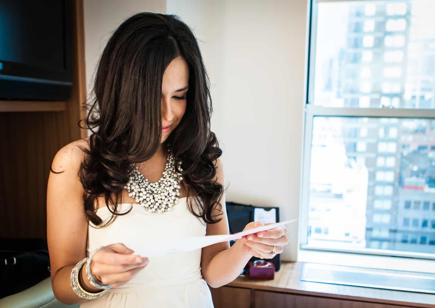 Bride reading letter from groom in hotel room