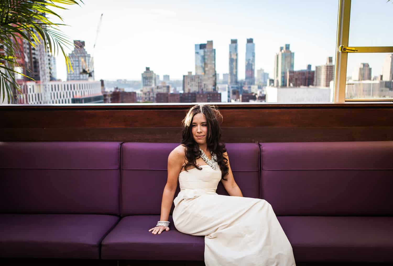 Bride sitting on bench with view of Upper West Side in background