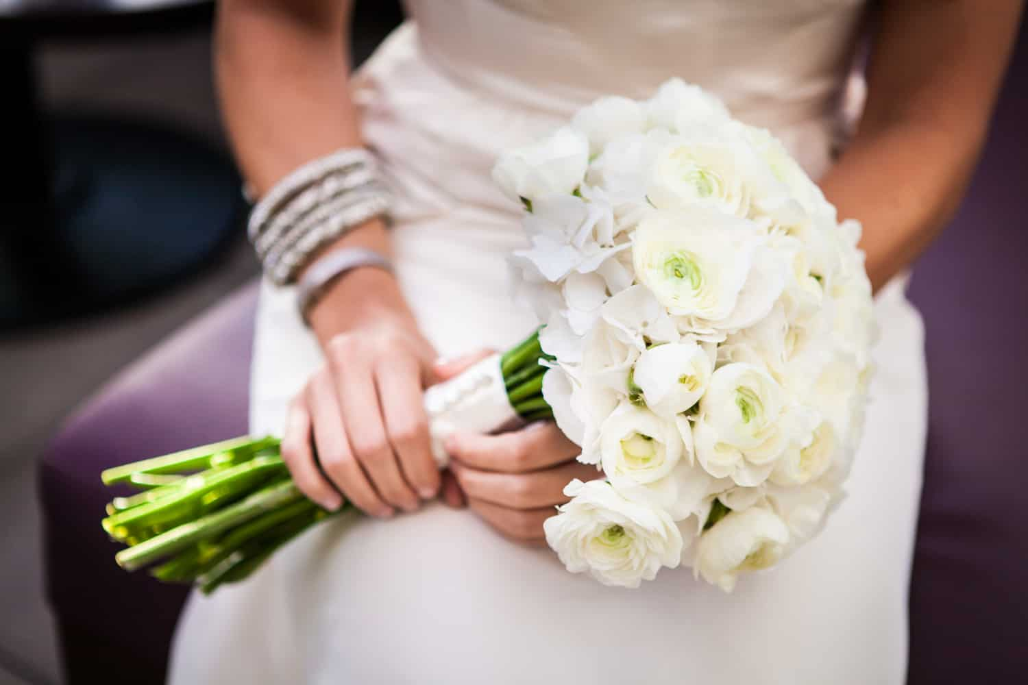 Close up of bride's hands holding flower bouquet