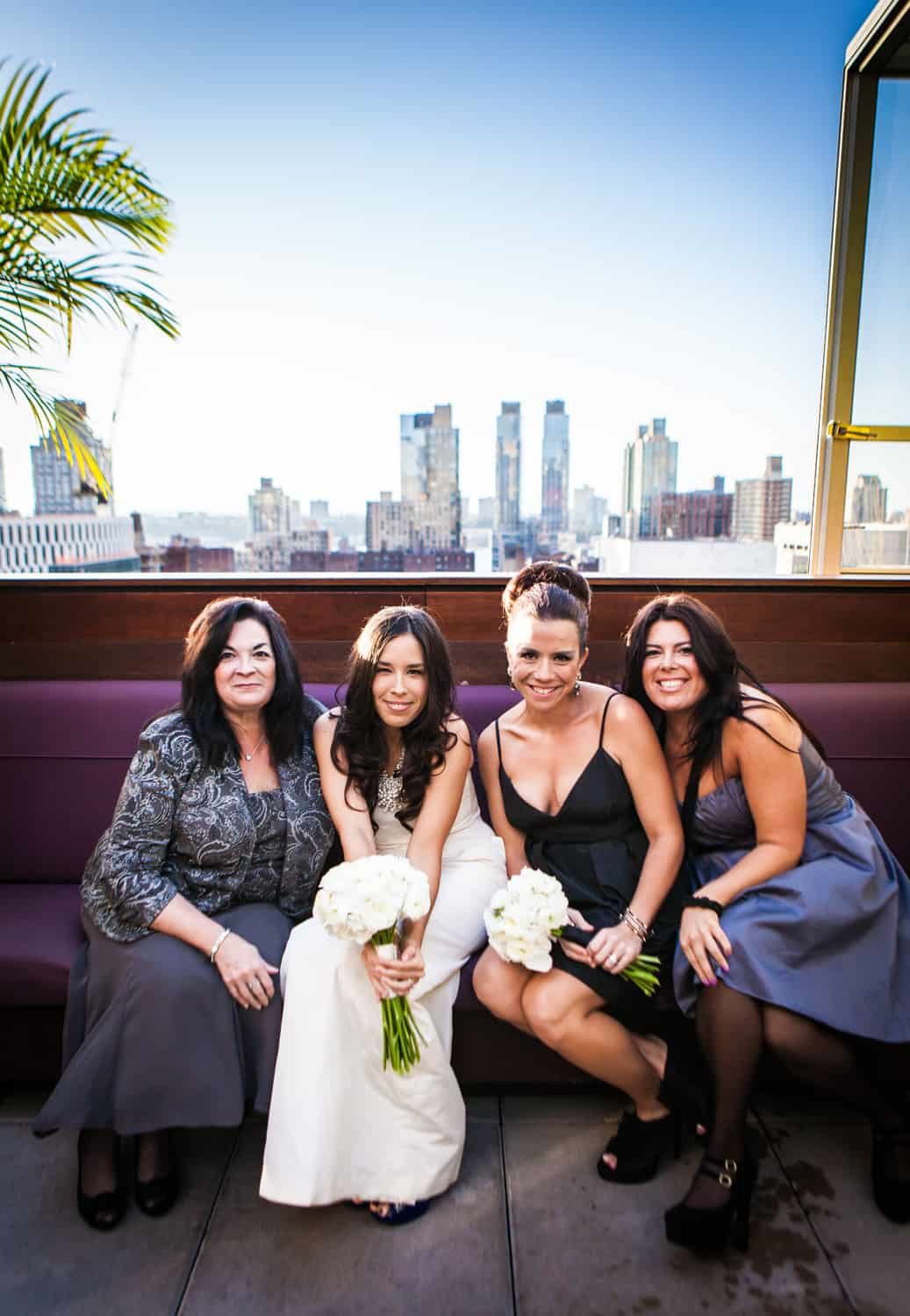 Bride and bridesmaids sitting on bench