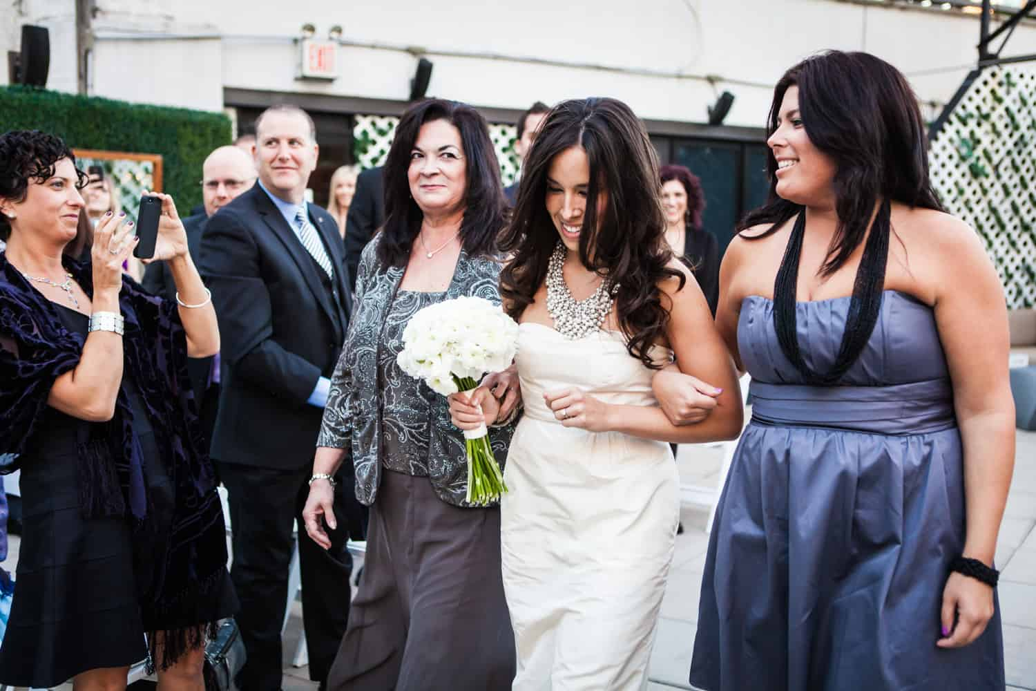 Bride, mother, and sister walking down aisle at an Empire Hotel rooftop wedding
