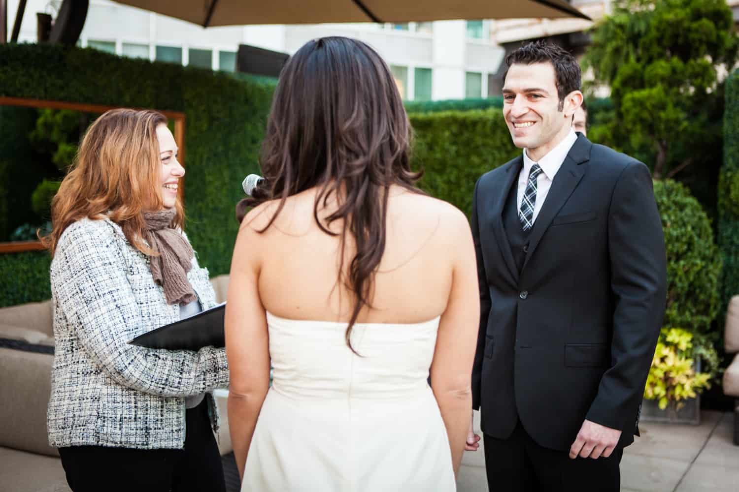 Groom seeing bride for first time during ceremony at an Empire Hotel rooftop wedding