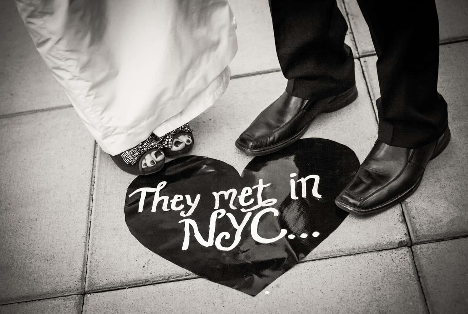 Black and white photo of couple's feet in front of heart-shaped 'They Met in NYC' sign on ground