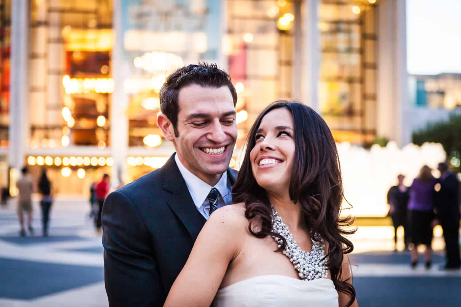 Bride and groom standing in front of Lincoln Center