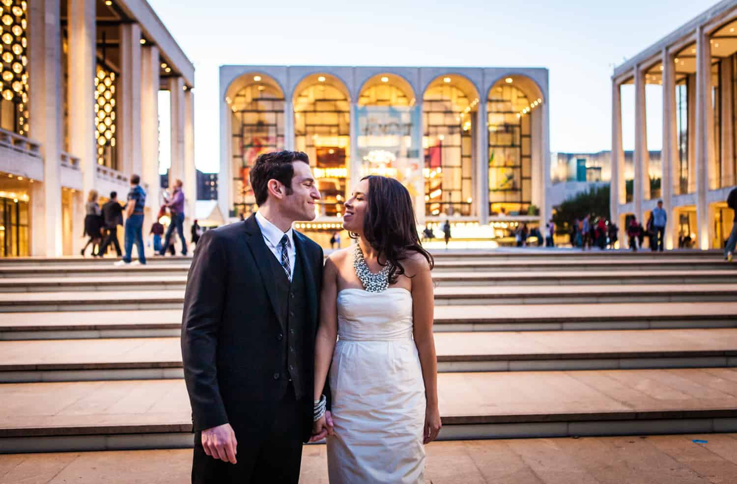 Bride and groom holding hands in front of Lincoln Center