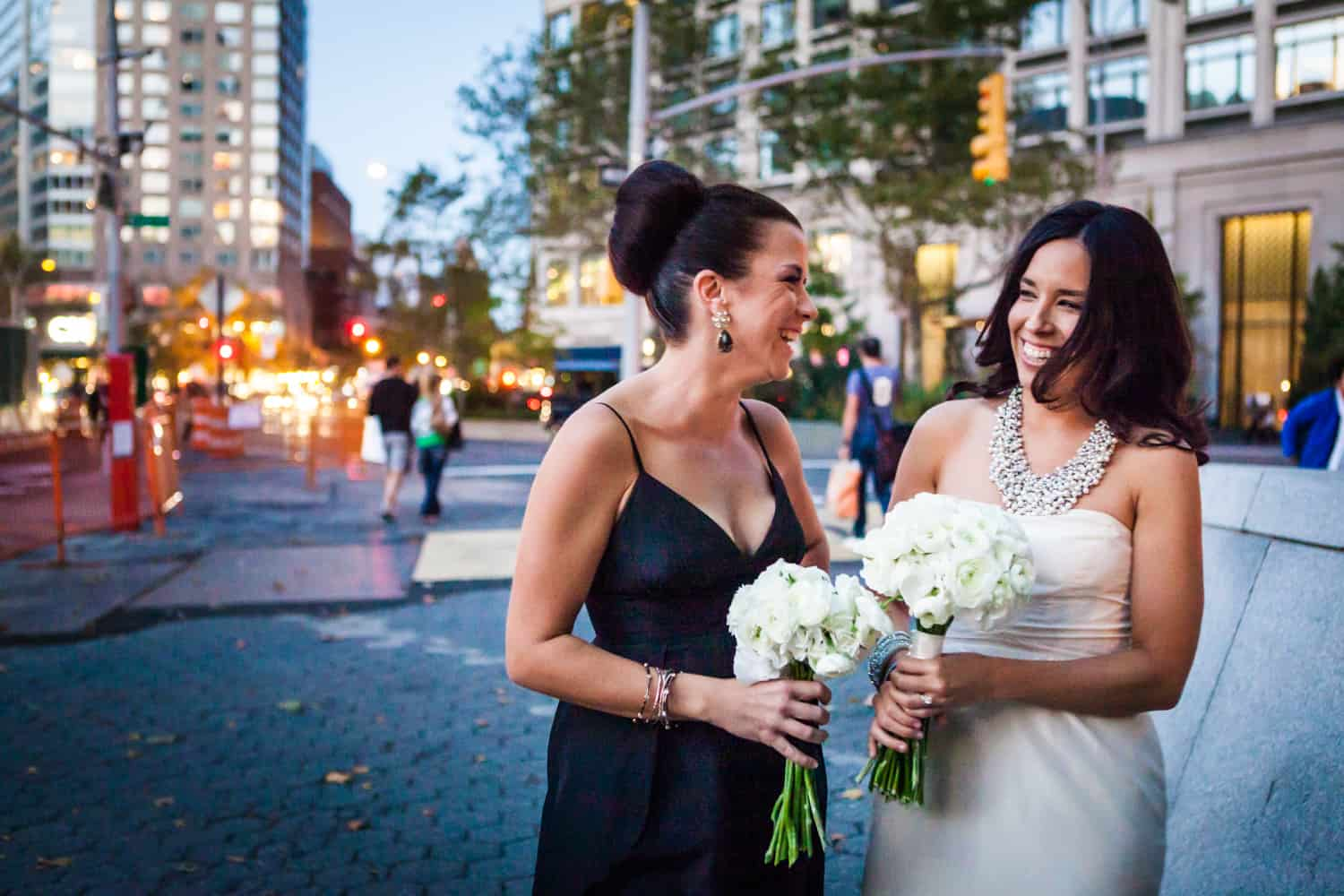 Bride and bridesmaid laughing on Upper West Side street