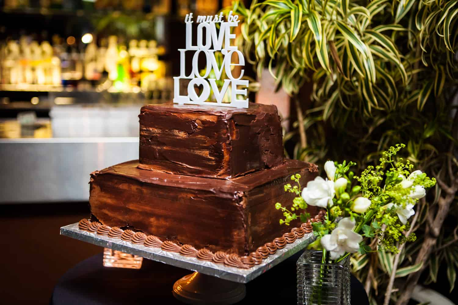 Chocolate, two-layer wedding cake with 'Love, Love, Love' topper