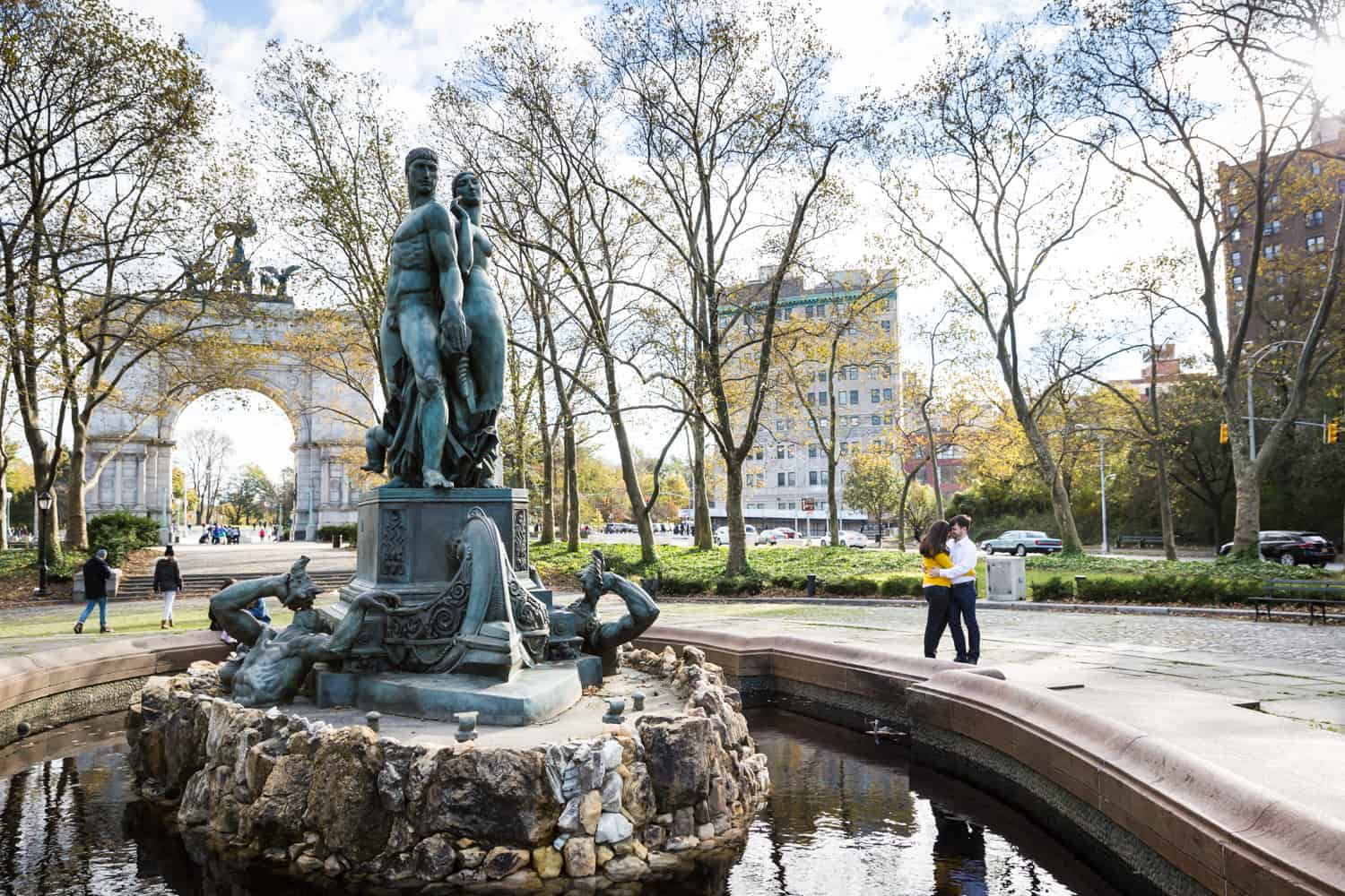 Grand Army Plaza engagement photos of couple hugging beside fountain