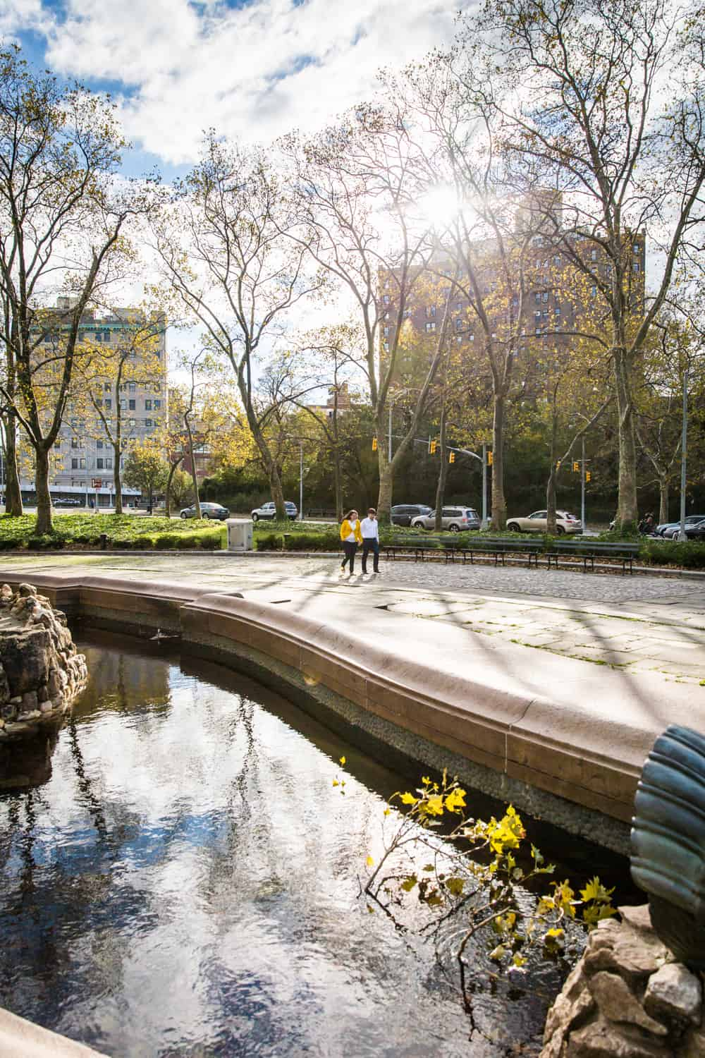 Grand Army Plaza engagement photos of couple walking around fountain