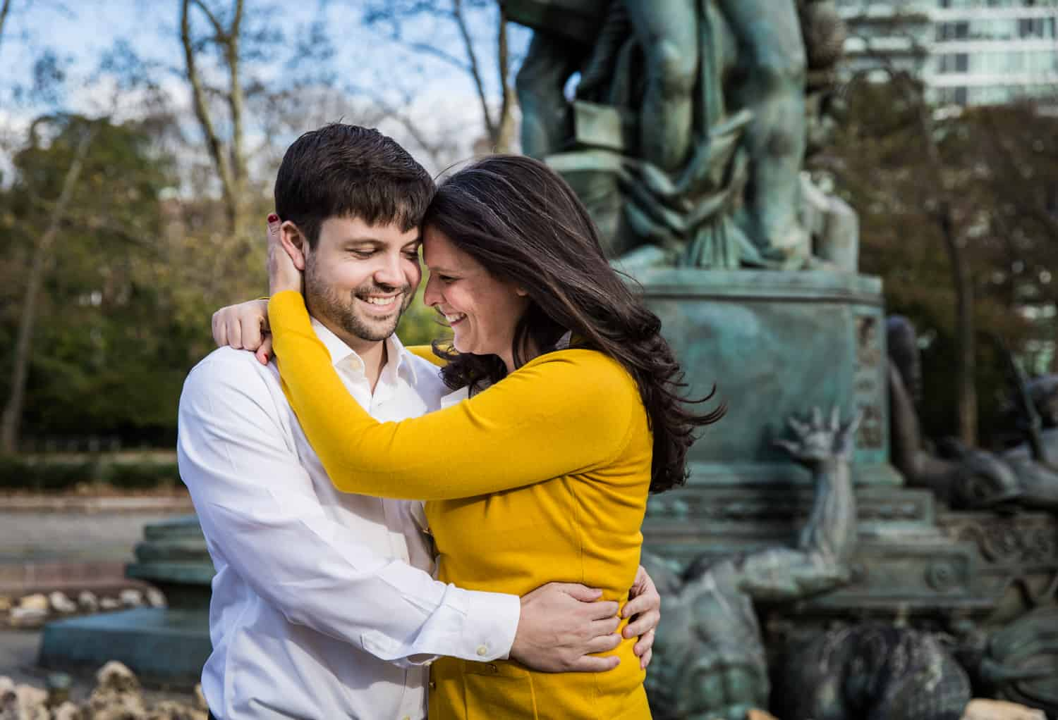 Grand Army Plaza engagement photos of couple hugging in front of fountain statue