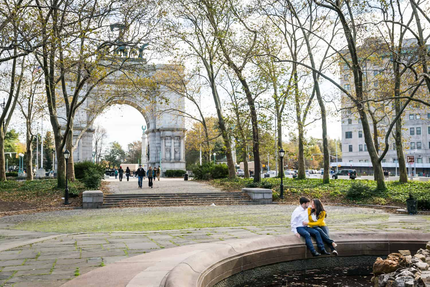 Grand Army Plaza engagement photos of couple sitting on side of fountain