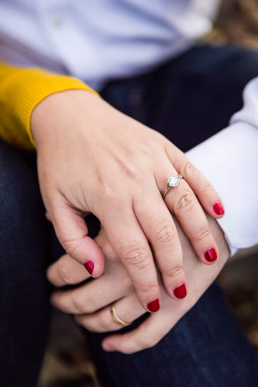 Close up of couple's hands with woman wearing engagement ring