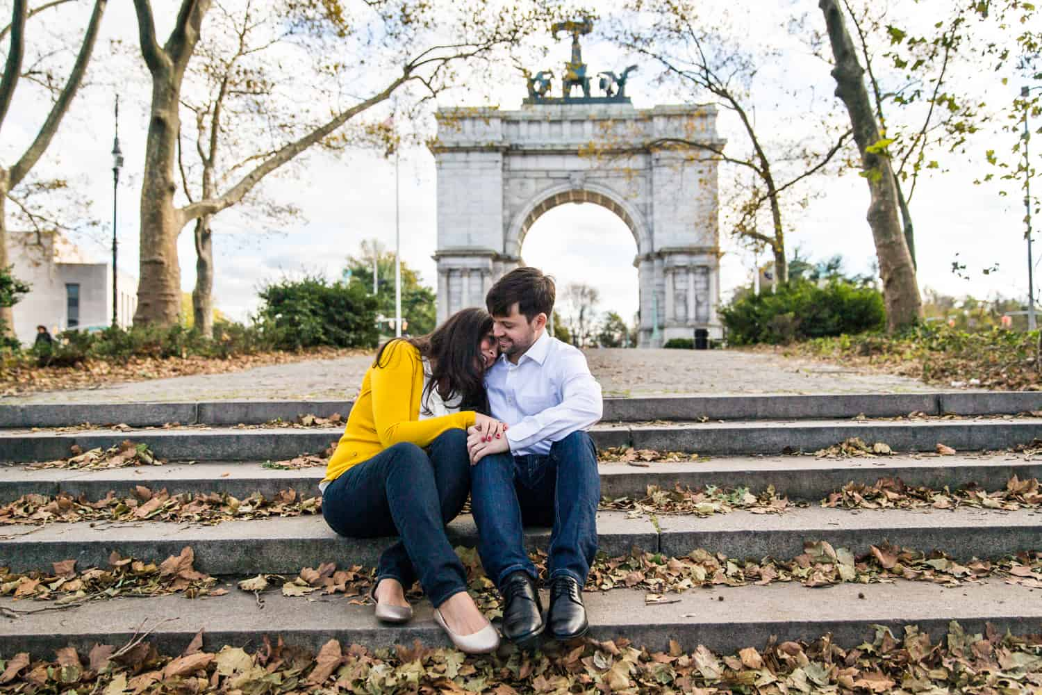 Grand Army Plaza engagement photos of couple sitting on steps