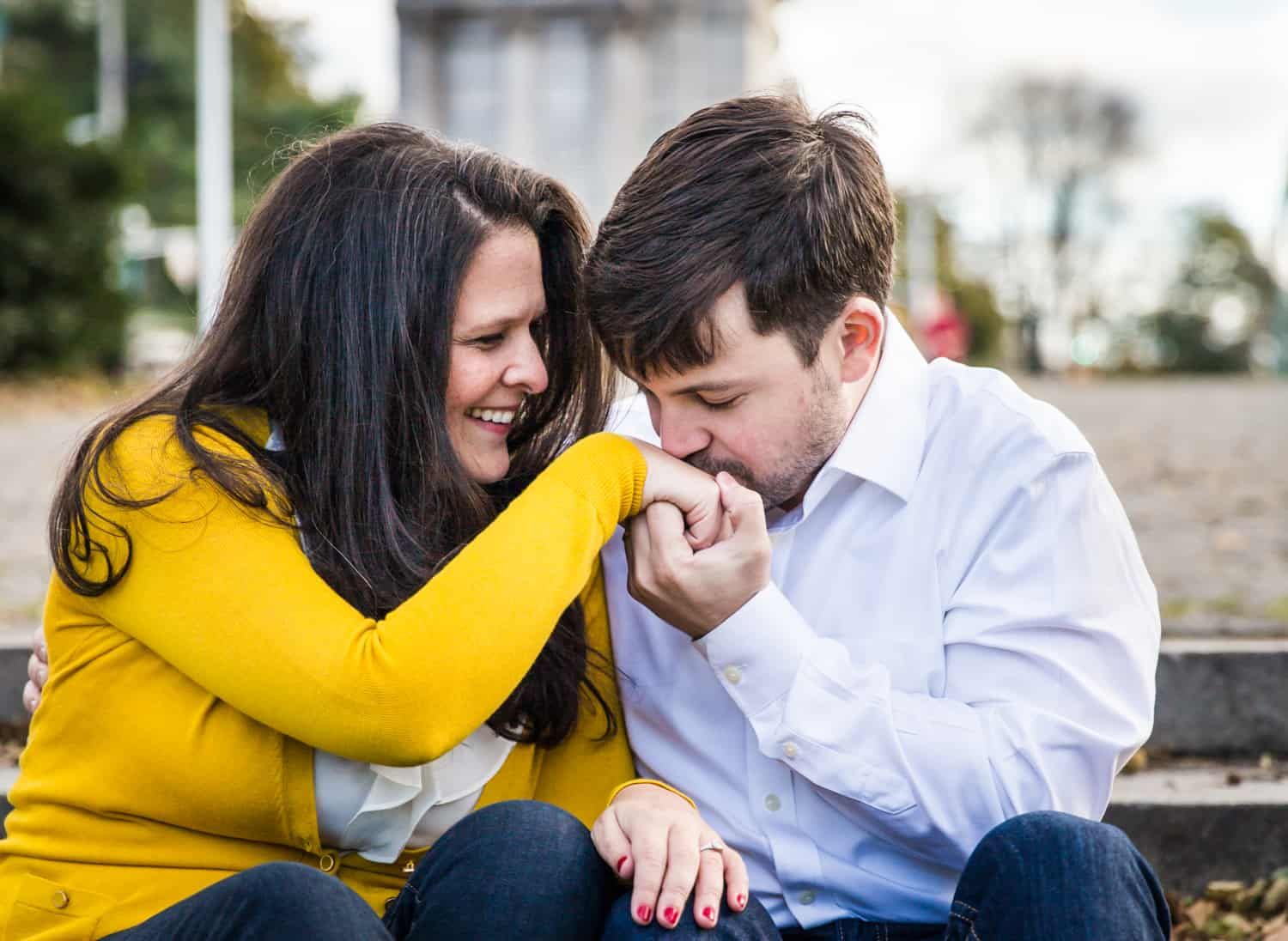 Grand Army Plaza engagement photos of man kissing woman's hand