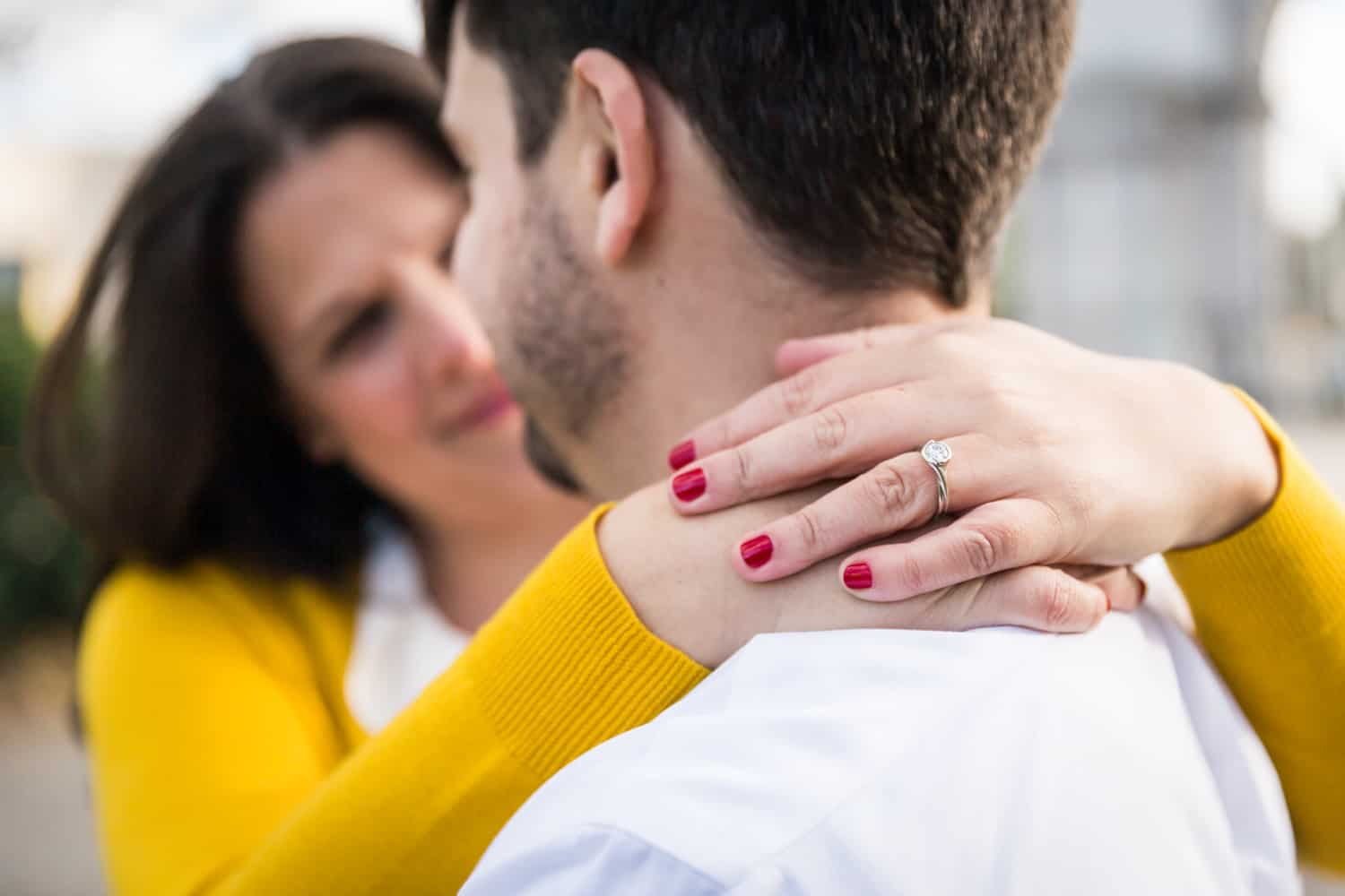 Close up of woman's hands wearing engagement ring around man's neck