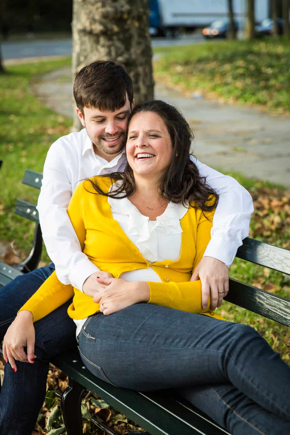 Grand Army Plaza engagement photos of couple laughing on bench