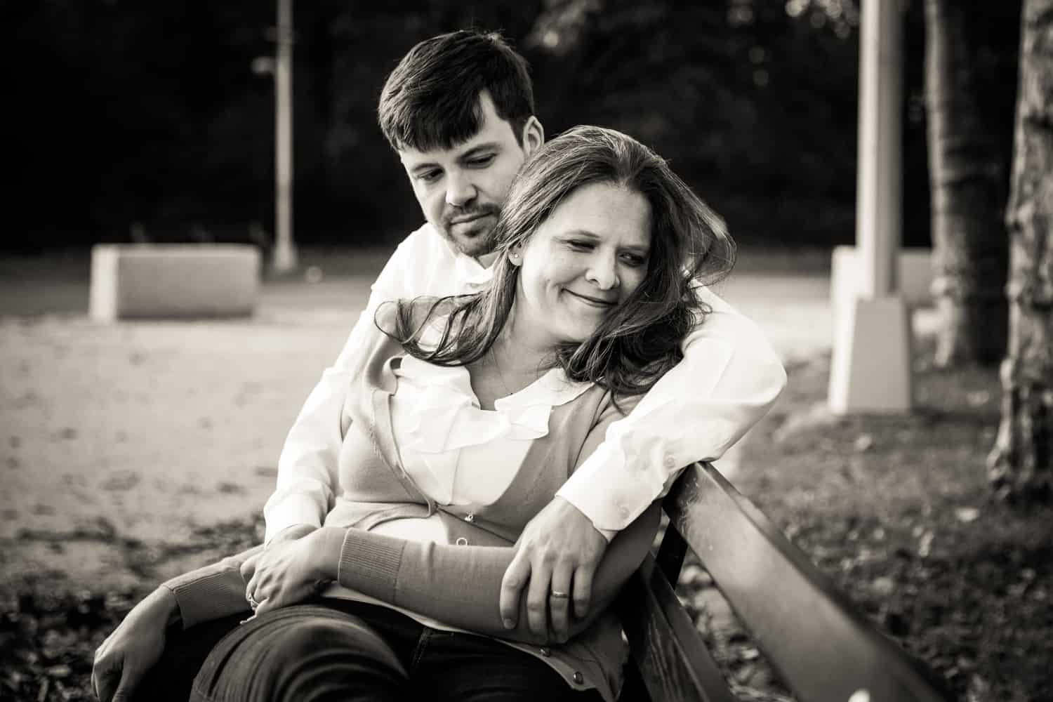 Black and white photo of couple cuddling on bench in Grand Army Plaza