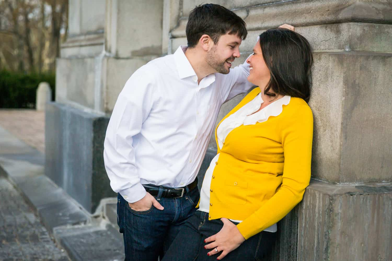 Grand Army Plaza engagement photos of couple leaning against arch