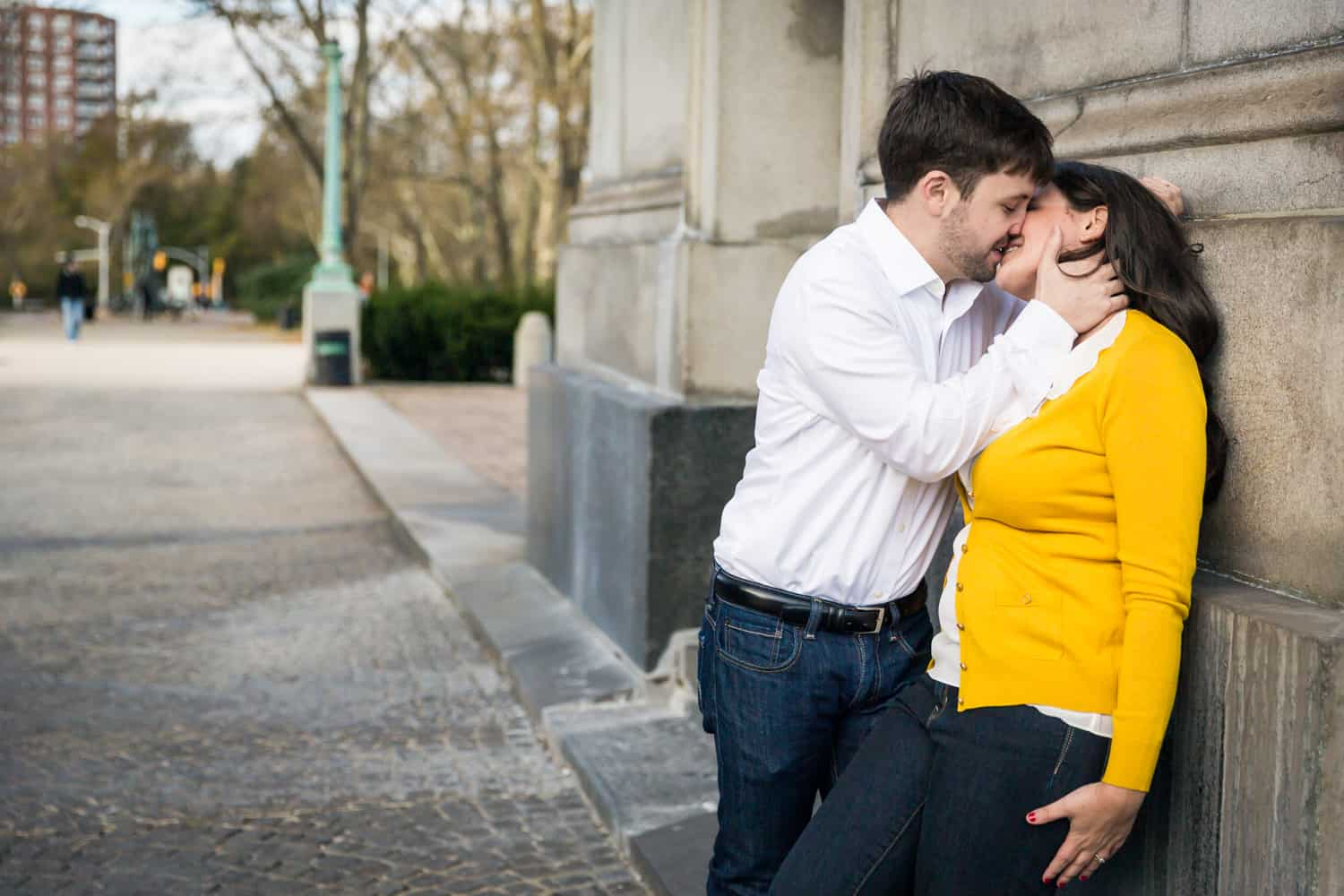 Grand Army Plaza engagement photos of couple kissing up against arch