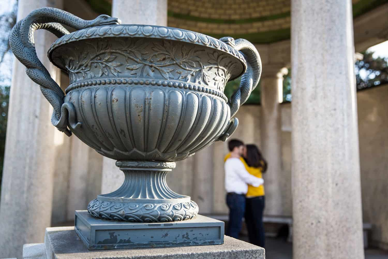 Planter urn with kissing couple in background
