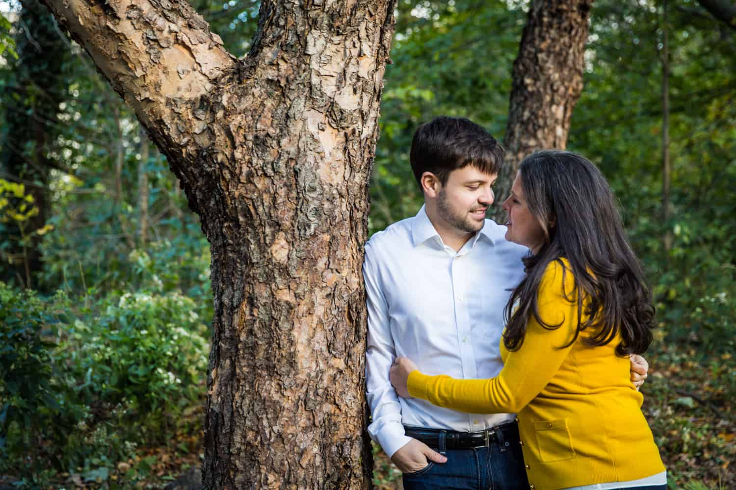 Couple hugging against tree in Prospect Park