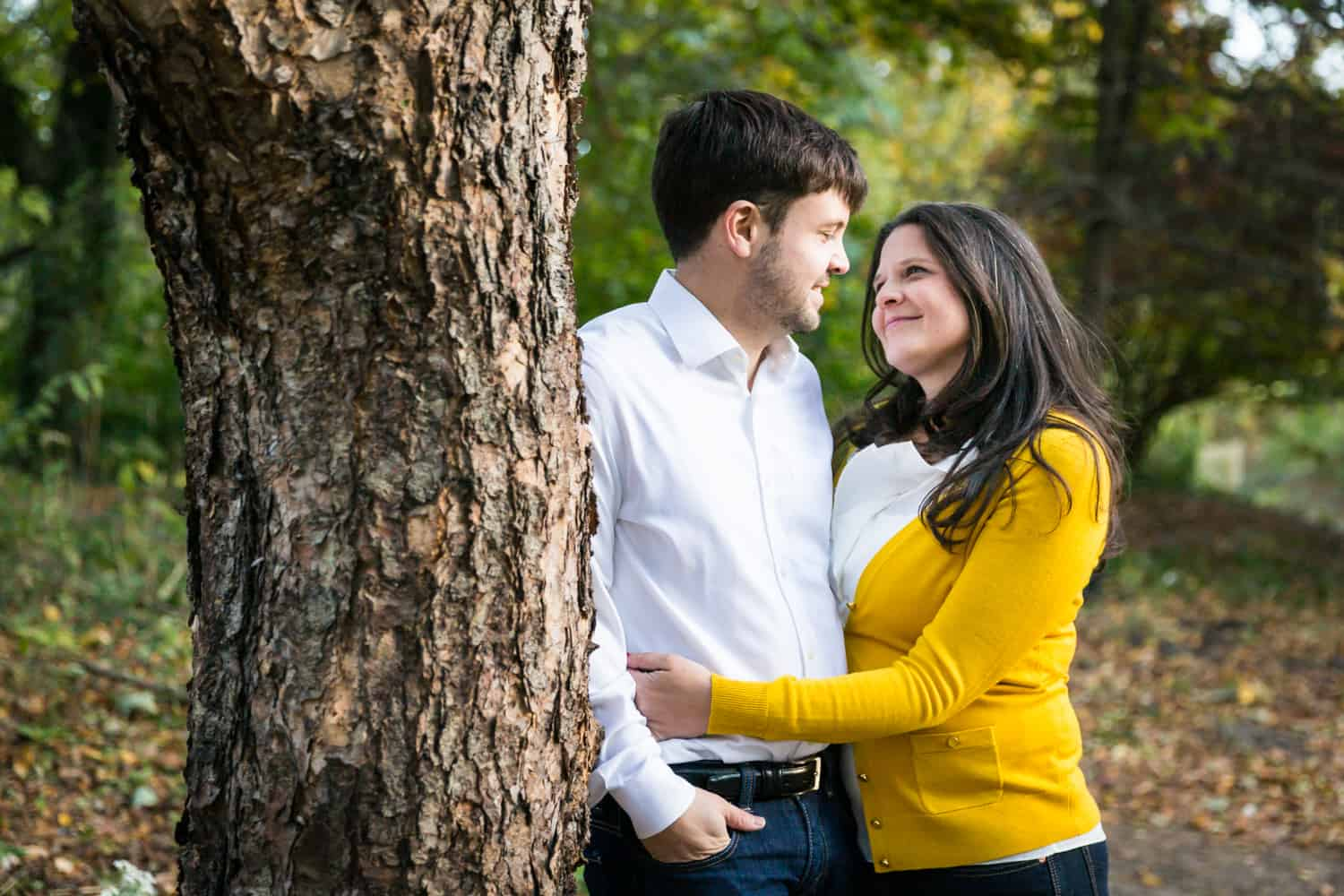 Couple cuddling next to tree in Prospect Park