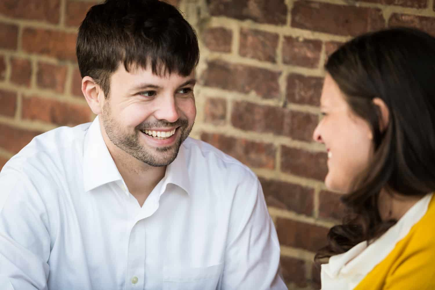 Couple laughing in front of brick wall