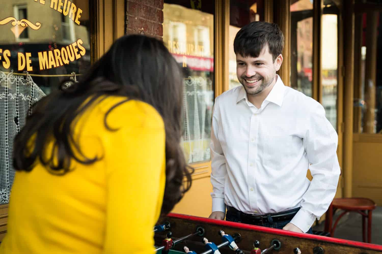 Couple playing foosball outside of restaurant