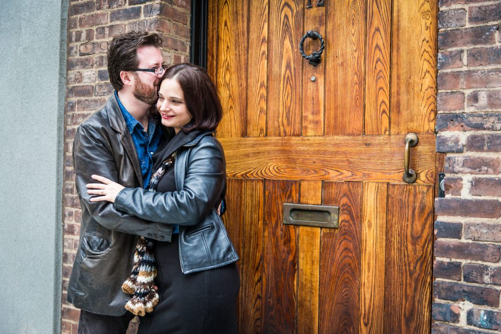 Couple in front of wooden door in Washington Mews during a Greenwich Village engagement session