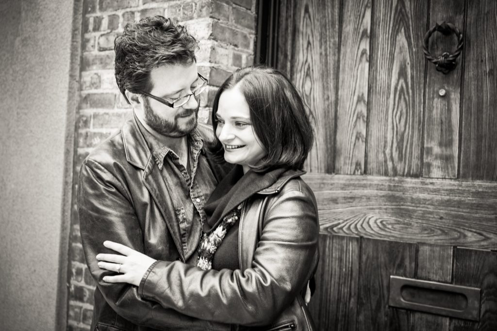 Black and white photo of couple in front of wooden door