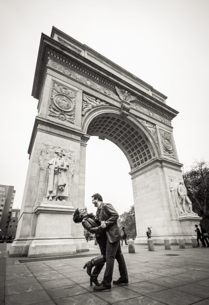 Black and white photo of couple dancing in front of Washington Square Arch