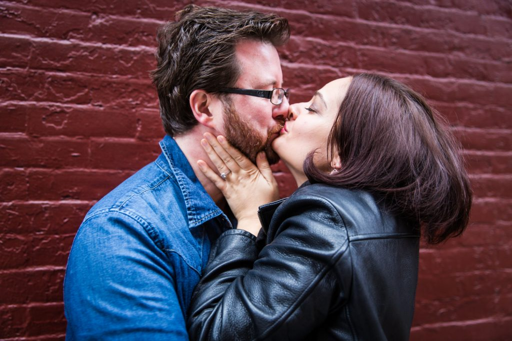 Couple kissing against brick wall in Greenwich Village