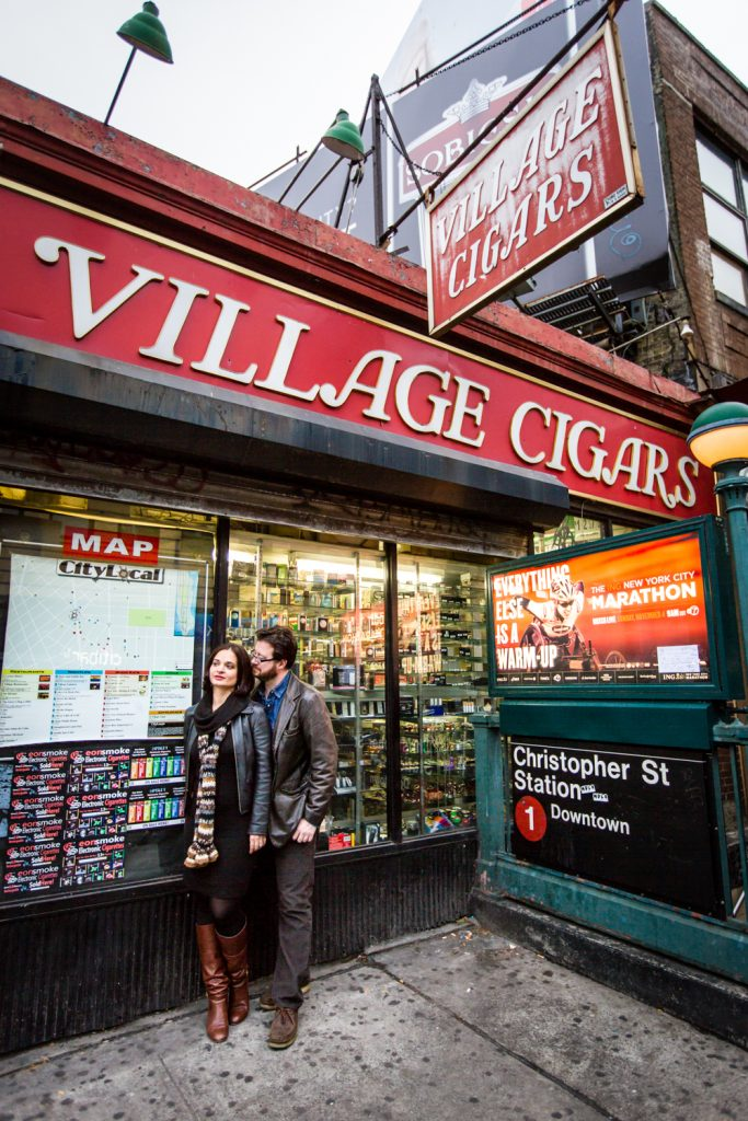 Couple standing under Village Cigars sign in Greenwich Village