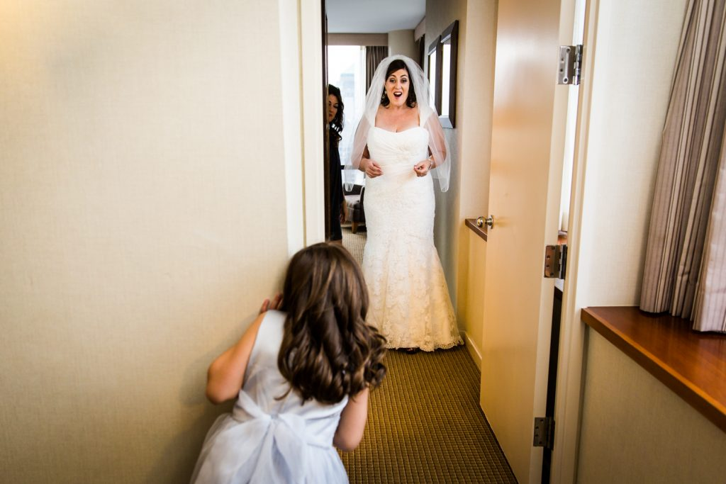 Little girl seeing bride walk down hallway