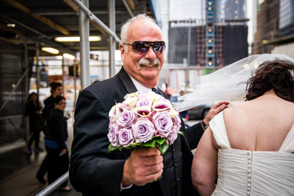 Man wearing sunglasses and holding a bride's bouquet