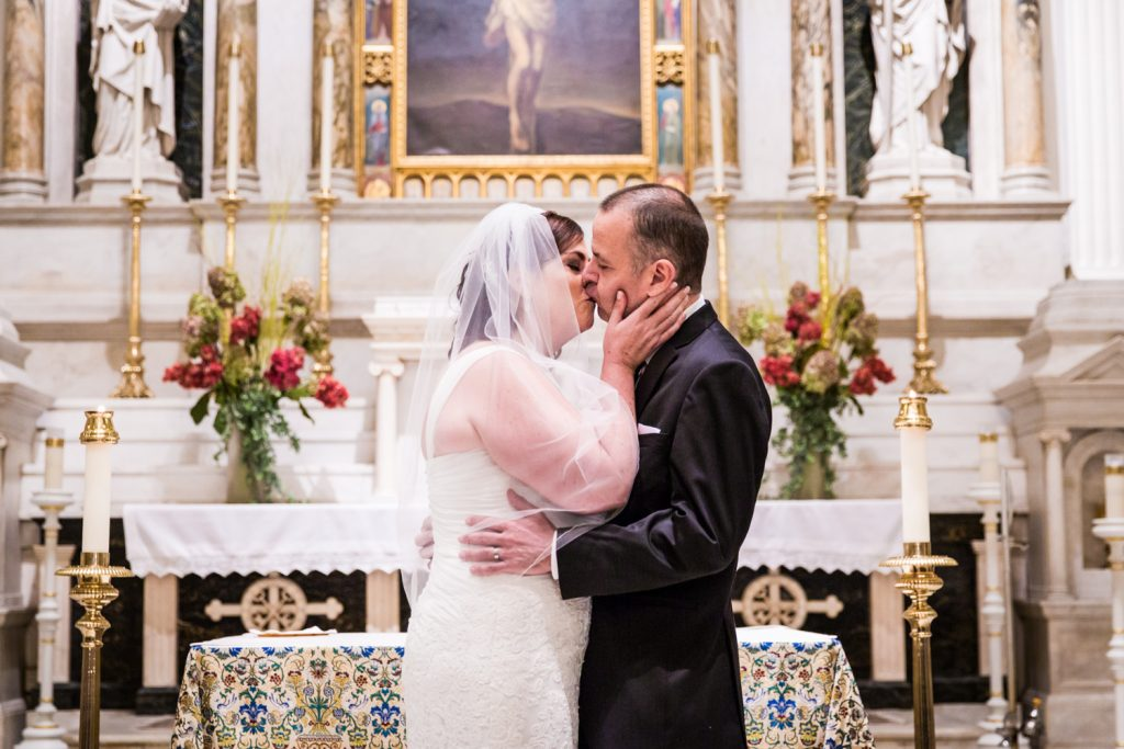 Bride and groom kissing at St. Peter's Church wedding