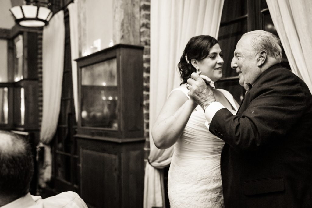 Bride dancing with father in black and white