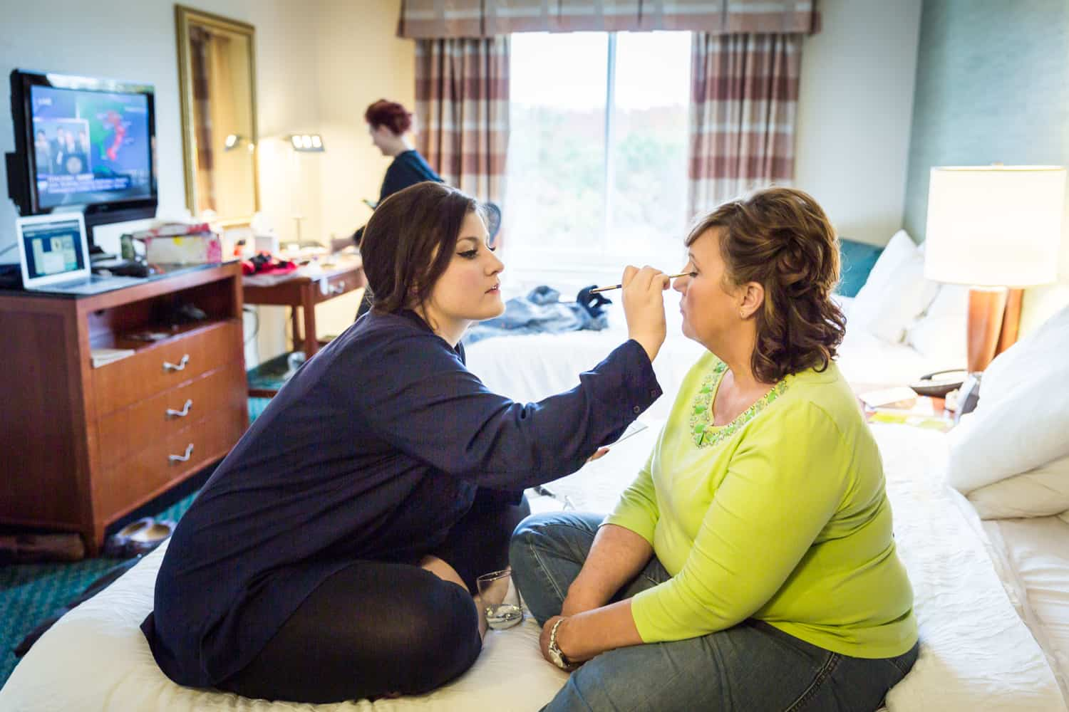 Woman putting makeup on mother of bride on hotel bed