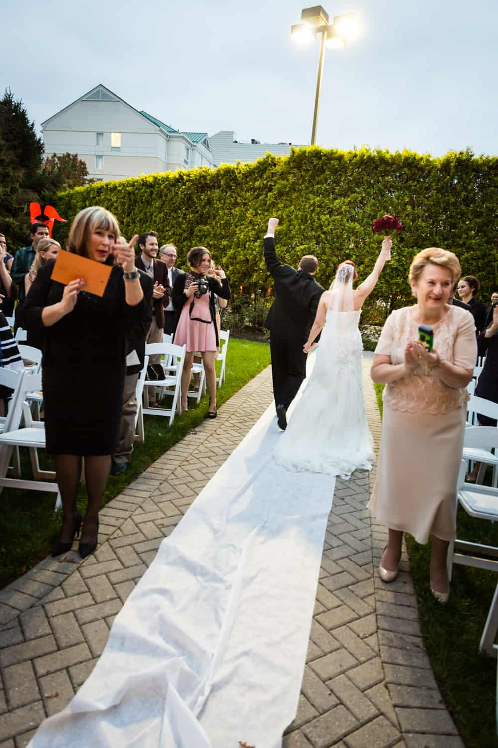 Nicotra's Ballroom wedding photos of bride and groom leaving ceremony with fists in the air