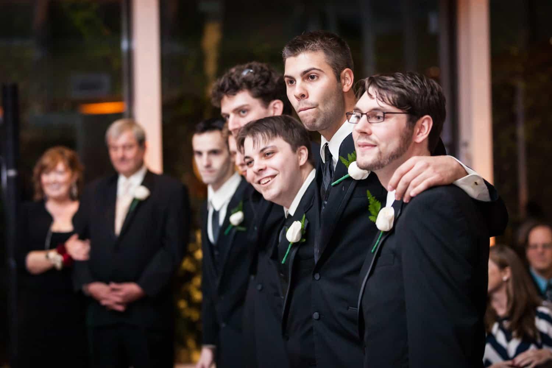 Nicotra's Ballroom wedding photos of groomsmen hugging and listening to speeches
