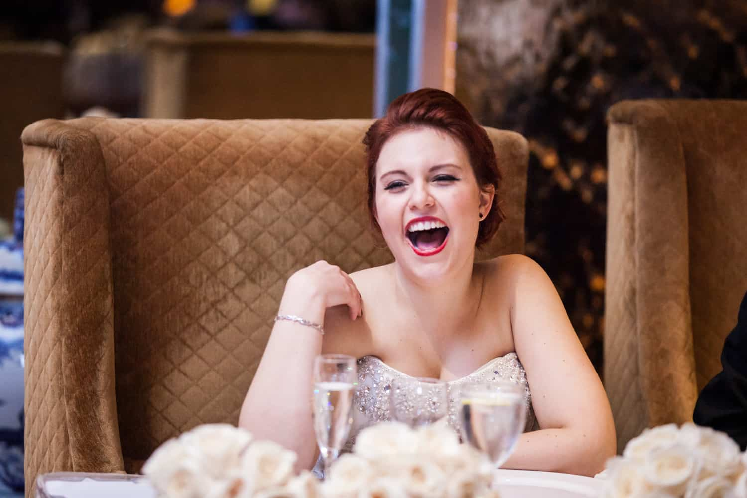Bride sitting at table and laughing
